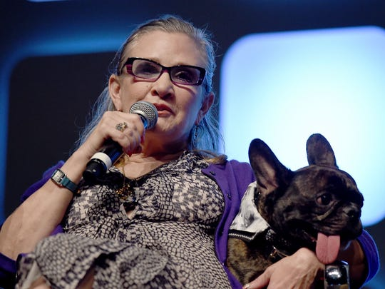 Carrie Fisher and her dog Gary on stage during a panel