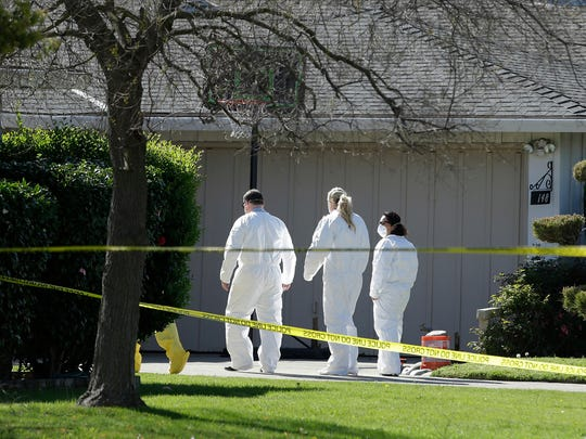 Investigators on Thursday walk to the home where four