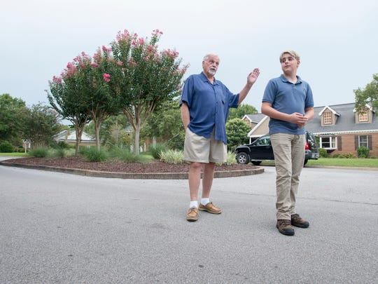 Greg Yost, left, talks on Wednesday, Aug. 23, 2017, about how his 15-year-old neighbor Jack Menzies performed CPR to save his life at this spot near their homes in Pensacola.