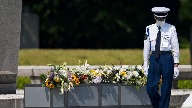 A policeman checks the flowers at the cenotaph at the Hiroshima Peace Memorial in Hiroshima on May 27, 2016. President Obama was to make history later on May 27 when he travels to Hiroshima -- becoming the first sitting U.S. leader to visit the site that ushered in the age of nuclear conflict.