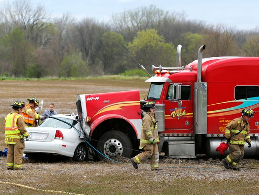Firefighters work to extricate the driver of a late model sedan after it collided with a semi trailer Wednesday, April 30, 2014, just north of the intersection of U.S. 231 and County Road 625 South. The driver of the sedan was airlifted to an Indianapolis hospital. The driver of the semi was taken to a local hospital.