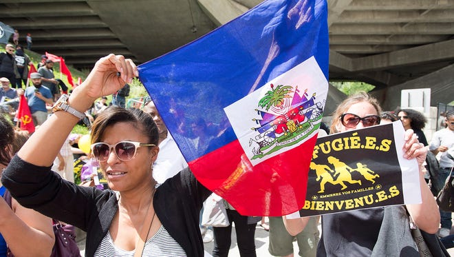 A woman holds up a Haitian flag in support of asylum seekers during a rally outside the Olympic Stadium in Montreal. The stadium is being used as a temporary shelter for some of the hundreds of asylum claimants pouring across the U.S-Canadian border.