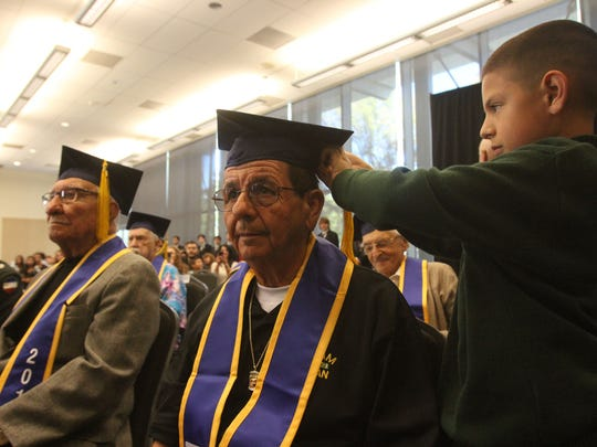 Grandson David Peña Jr., fixes Juan Peña's tassel during