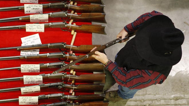 A man looks at antique guns at the Great Falls Gun and Antique Show at the Four Seasons Arena.