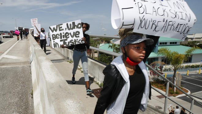 Protesters march across the Dunlawton Bridge in Port Orange, Sunday, May 31, 2020.
