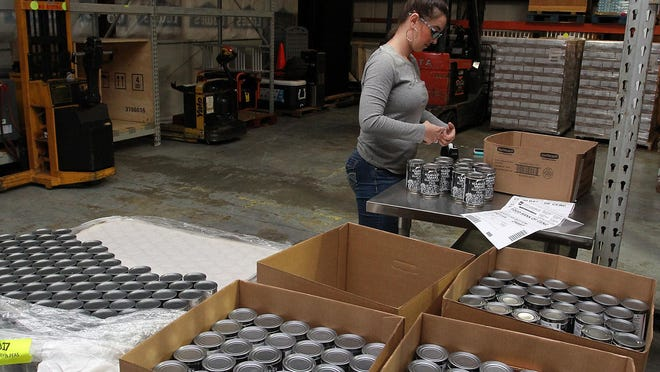 Kelly Carroll volunteers to place required labels on food cans at the Food Bank of Central and Eastern North Carolina in New Bern.