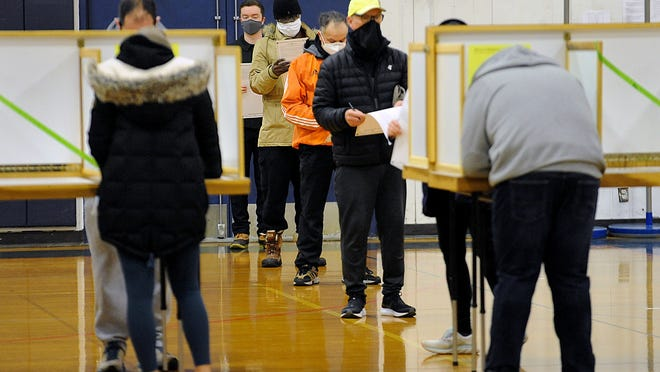 Framingham voters wait in line for available voting booths at the Keefe Technical High School voting place in Framingham, Nov. 3, 2020.