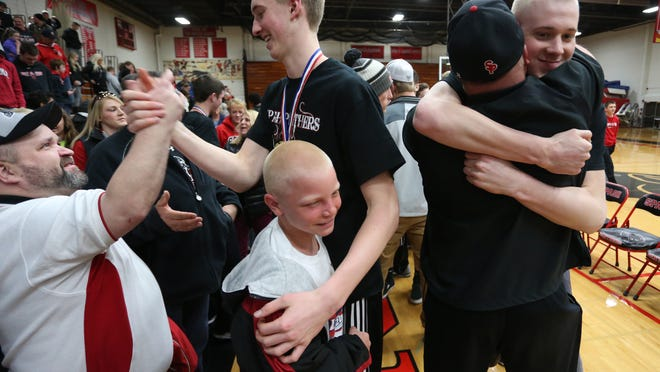 Brothers Sam Hauser, center, and Joey Hauser, right, get congratulated by fans at SPASH, Sunday, March 22, 2015, as the team and fans celebrated their WIAA Division 1 boys' state basketball championship.