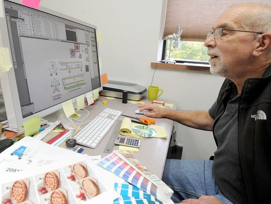 Graphic designer Brad Cook looks at a design on his