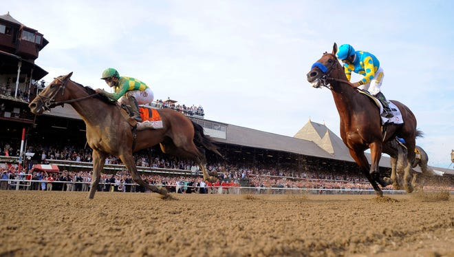 Keen Ice, left, with jockey Javier Castellano, moves past Triple Crown winner American Pharoah, with Victor Espinoza, to win the Travers Stakes horse race at Saratoga Race Course in Saratoga Springs, N.Y., Saturday, Aug. 29, 2015. (AP Photo/Hans Pennink)