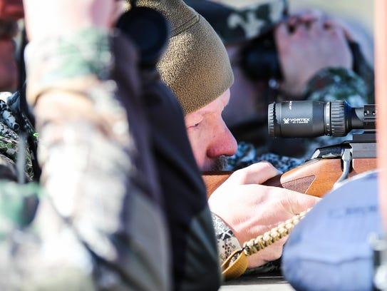 Army Sgt. 1st Class Richard Voss sights on a rifle