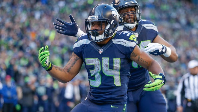 Running back Thomas Rawls of the Seattle Seahawks is congratulated by fullback Will Tukuafu after scoring a touchdown against the San Francisco 49ers on Nov. 22, 2015, in Seattle.