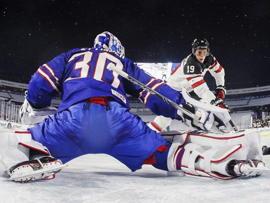 United States goalie Jake Oettinger (30) makes a save against Canada's Drake Batherson, right, in the shootout period at an IIHF World Junior Championship preliminary outdoor hockey game at New Era Field in Orchard Park, N.Y., Friday, Dec. 29, 2017. (Mark Blinch/The Canadian Press via AP)