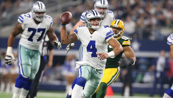 Dallas Cowboys quarterback Dak Prescott (4) scrambles against the Green Bay Packers in the NFC Divisional playoff game at AT&T Stadium.