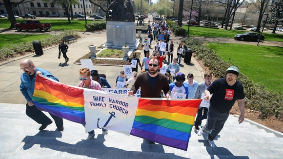 Members of Flowood's Safe Harbor Family Church lead a procession up the south steps of the state Capitol in Jackson during a rally against discrimination toward members of the state's LBGT community.