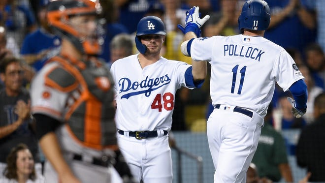 Los Angeles Dodgers' A.J. Pollock, right, celebrates a solo home run with Gavin Lux, center, during the second inning of a baseball game as San Francisco Giants catcher Buster Posey stands at left, in Los Angeles, Friday, Sept. 6, 2019. (AP Photo/Kelvin Kuo)