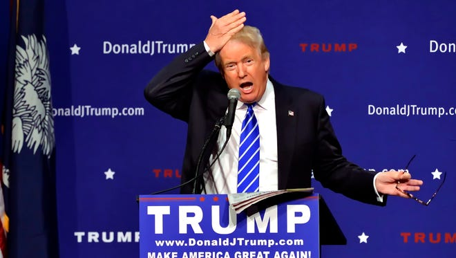 Donald Trump pulls his hair back to show that it is not a toupee while speaking during a rally on Aug.  27, 2015, in Greenville, S.C.