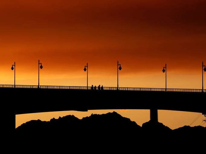 Pedestrians cross the Manette Bridge at sunset on Saturday,