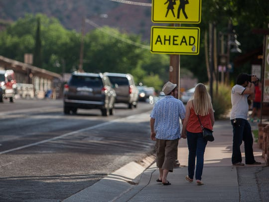 In this July 3, 2013 photo, shoppers stroll in downtown Springdale, Utah.