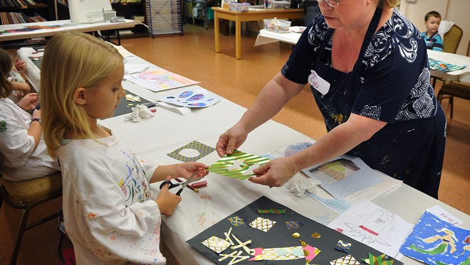 Cindy Thomas helps Elaina Amy, 6, as she uses scrapbook paper to create a rocket collage during Camp Creativity at the Kemp Center for the Arts Thursday. Campers learn about art, music and drama.