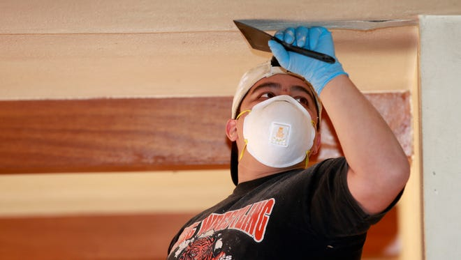 Team Depot volunteer Manny Martinez works on the Rowe family's house on Saturday in Farmington.
