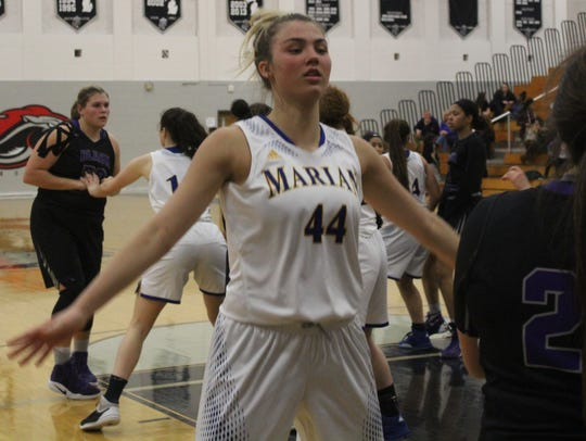 Marian's sophomore guard Olivia Moore (44) defends