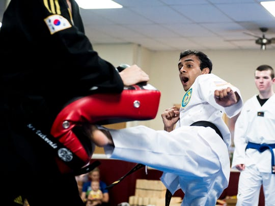 Tamour Bari, a 19-year-old black belt, kicks a pad held by Derek So, the lead instructor and owner of So's Taekwondo. The Hanover studio recently traveled to Detroit to compete at the USA National Championships where they finished with a combined 12 medals, including silver in board breaking for Bari.