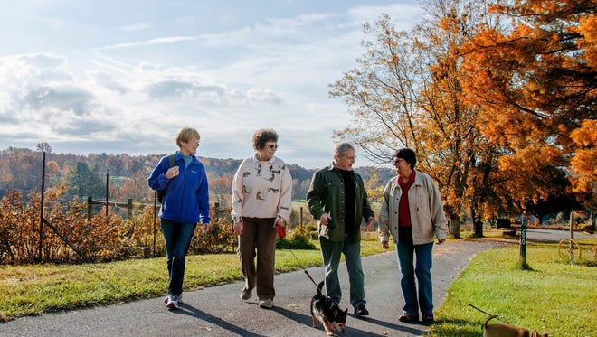 Residents enjoy conversation while taking a walk with pets at Uplands Village