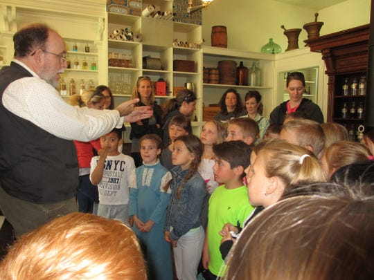 Students in second grade at Webster Elementary School learn from a presenter about the pioneer days during a field trip to Living History Farms.