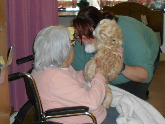 Community Life Coordinator Darlene Russell shows the Companion Pet cat to resident Pauline Kinley at Quincy Village in Waynesboro.