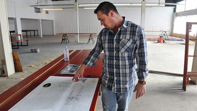 Matt Bitsche looks over the floorplan for Wichita Falls Brewing, a business endeavor he hopes to open later this year at the corner of Indiana and Seventh Street. The native Wichitan helped start Infamous Brewing Company in Austin in 2012.