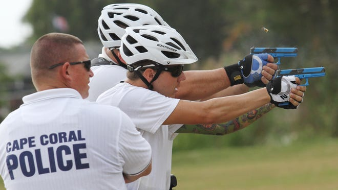 Chad Hartzell, right, fires his weapon while training during the Cape Coral Police Department's bike cop program on Tuesday.