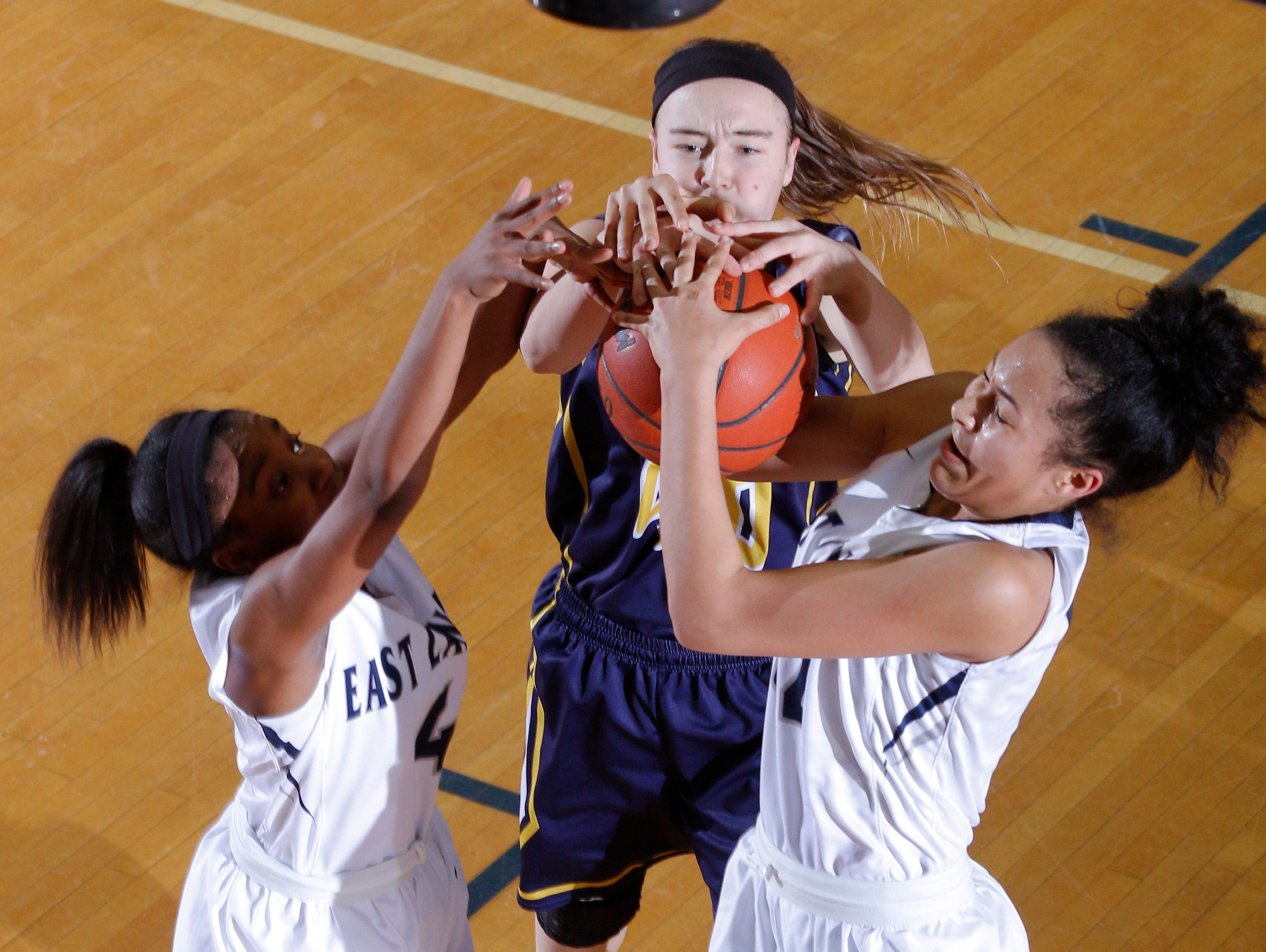 East Lansing's Sanaya Gregory, left, and Aaliyah Nye, right, and DeWitt's Madison Petersen, center, battle for a rebound during their district final game Friday, March 3, 2017, in East Lansing, Mich. East Lansing won 48-47.