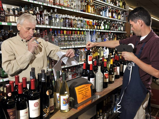 Goodrich's Shop-Rite co-owner and Wine and Spirits manager Steve Scheffel, left, and store employee Kirk Teichman, right, check in a wine and beer delivery order as the beverages are stocked at the store in East Lansing, Aug. 17, 2012. Scheffel said the store carried around 3,500 different labels of wine.