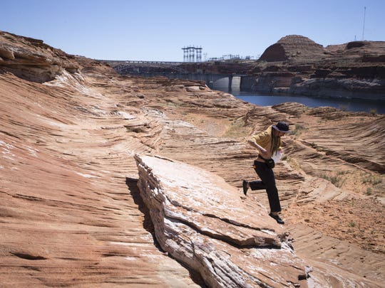A visitor hops down to Lake Powell at the Chains, April