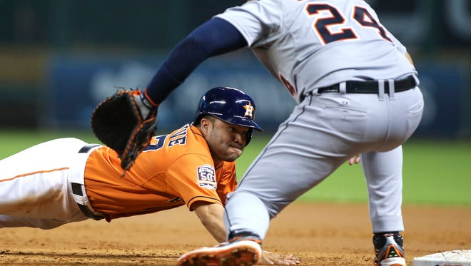 Astros second baseman Jose Altuve dives into first base on a pickoff attempt as Tigers first baseman Miguel Cabrera fields the throw during the third inning of the Tigers' loss Friday in Houston.