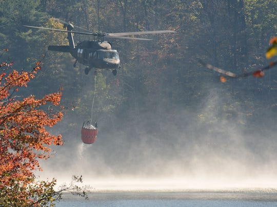 A national guard chopper scoops out water from the lake at the Table Rock State Park Visitors Center to dump on the 100 acre forest fire on Pinnacle Mountain, which is only 10 per cent contained.