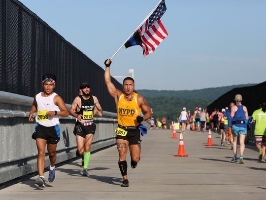 Armando Urbina of Mineola carries the American flag as he makes his way across the Walkway over the Hudson in the Walkway Marathon June 11, 2017 in Poughkeepsie.