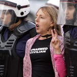 In this 2012 file photo, riot police arrest U.S. activist Medea Benjamin during a protest march by Bahraini women in Qadam, Bahrain. The co-founder of U.S.-based anti-war group CodePink says Egyptian police detained her at the Cairo airport Tuesday when she tried to enter the country and assaulted her, fracturing her shoulder, as they handcuffed her before deporting her.
