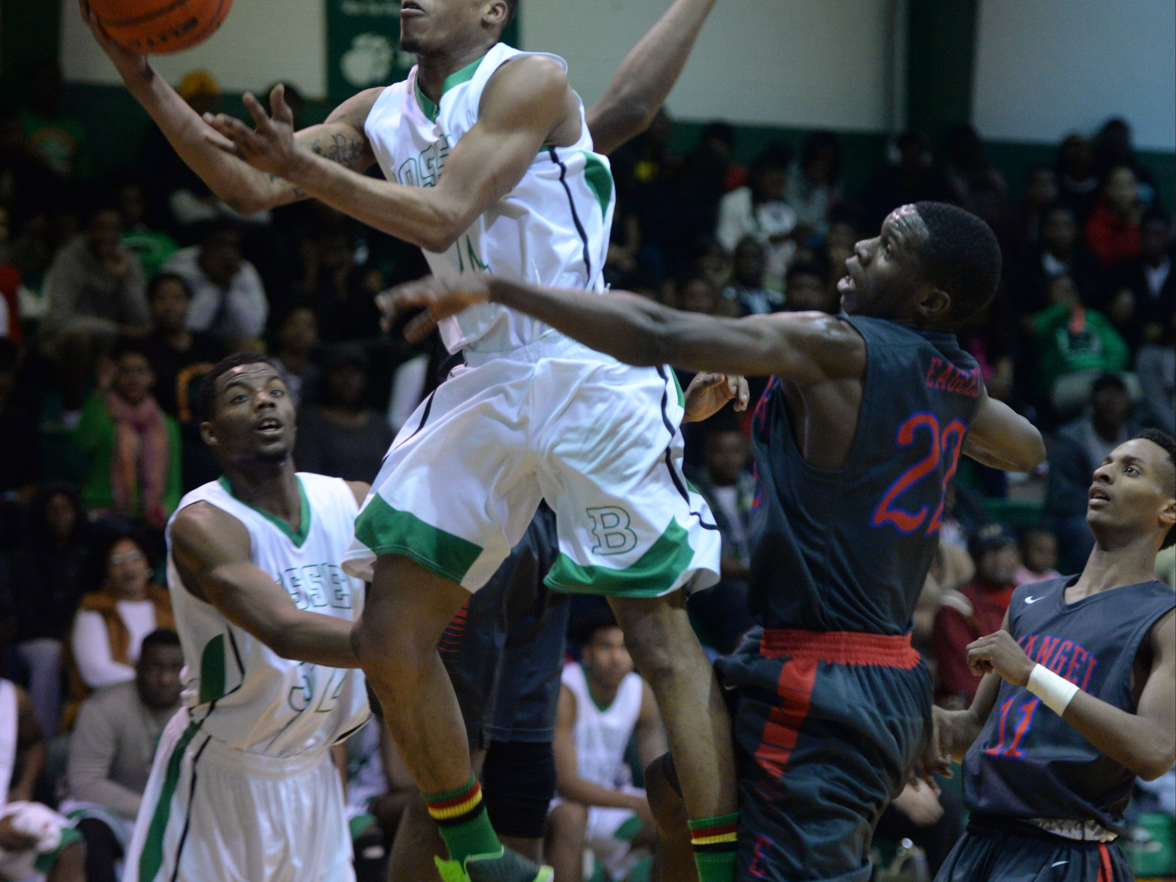 Bossier's Kentrell Hardey splits a pair of Evangel defenders, misses the layup but draws a foul during Bossier's 54-37 win Tuesday night. With Bossier win over Evangel they now force a tie for the 1-3A title.