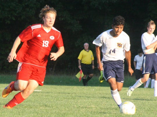 John Glenn's Justin Brown (19) and Wayne's Miguel Martinez race to the ball.