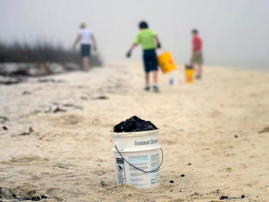 Ocean Hour volunteers clean up asphalt along Park West at Pensacola Beach last year. Ocean Hour is one of eight environmental organizations that are coming together to form the Emerald Coast Clean Waters Alliance.