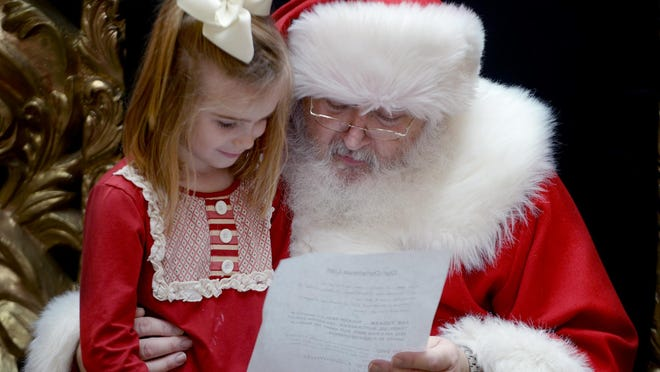 Emily Davenport shows Santa her Christmas list in this Sun file photo taken at the Old Hickory Mall.
