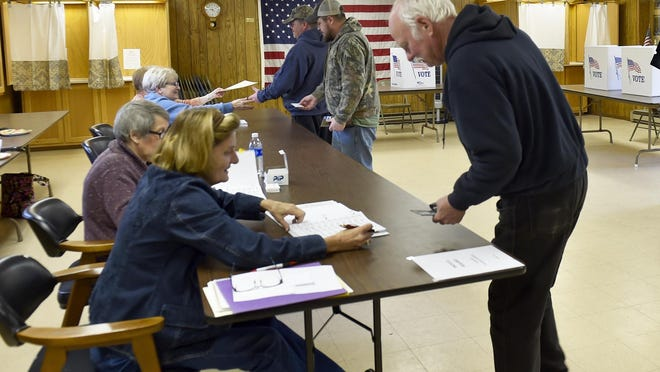Voting was steady Tuesday morning at the Forestville Town Hall in Maplewood as Lee Ellison, right, shows a photo ID card. Ahead of him in the line are Rick Krueger and his son, Mitchell.