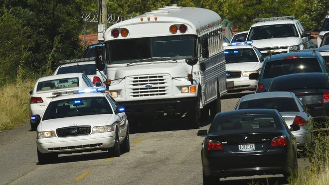 Police officers escort UPS employees on a bus from the scene where three people were killed, including the gunman, at a UPS facility in Birmingham, Ala., Tuesday, Sept. 23, 2014.  (AP Photo/ Al.com, Joe Songer)