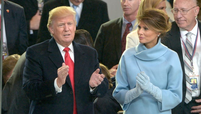 President Trump and first lady Melania Trump applaud during the traditional Inaugural Parade.