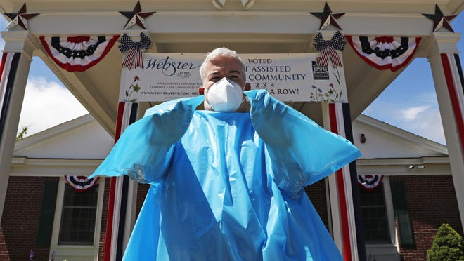 Brendan Williams, president of the New Hampshire Health Care Association, wears an isolation gown with no sleeve openings for hands, which was received in a shipment from the federal government, outside Webster at Rye senior care center on Wednesday, July 1, 2020, in Rye. The problematic gowns, child-sized examination gloves and surgical masks with ear loops that break when stretched make up the bulk of the personal protective equipment recently sent by the Federal Emergency Management Agency to New Hampshire nursing homes, according to Williams. The facility is not using the items they received from FEMA.