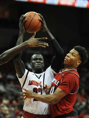 Louisville's Deng Adel (center) is fouled by the Red team on Friday during the second Red-White scrimmage at the KFC Yum! Center. Oct. 27, 2017