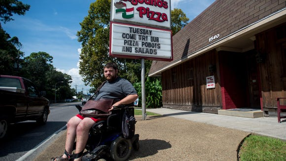 Liam Doyle poses for a photograph at the front entrance at Bisbano's Pizza in Lafayette. Doyle and the nonprofit Advocacy Center are suing Bisbano's Pizza for non-compliance with the Americans with Disabilities Act.