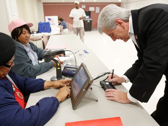 Poll workers Bertha Moses, left, and Florine Williams, check Mississippi Gov. Phil Bryant's driver's license Nov. 3 in a Jackson precinct as part of the voter ID procedure. A move to push early voting and online voter registration died this year in the Legislature.